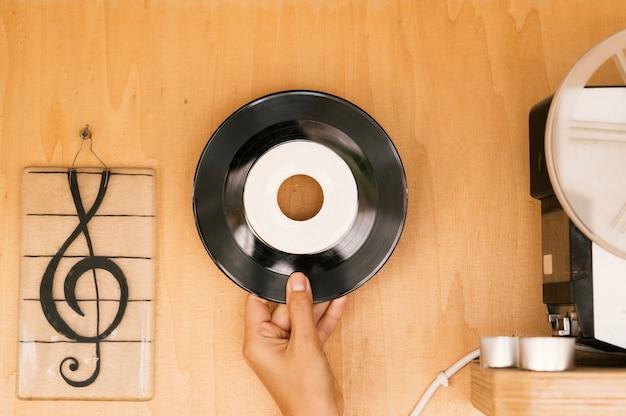 木製のテーブルにビニールディスクを持っている人 無料写真