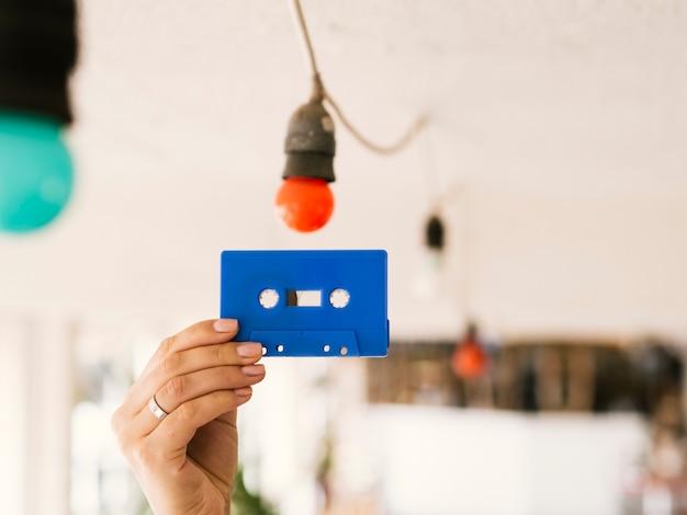 カセットテープを高く保持している人 無料写真