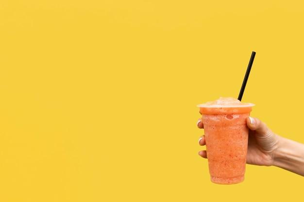 背景が黄色の飲料を持っているクローズアップ手 無料写真