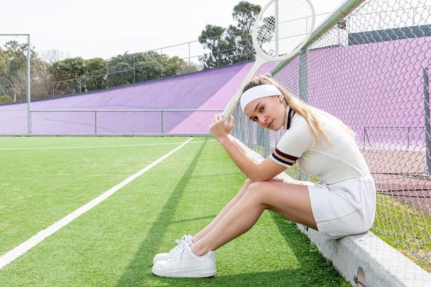 Длинный выстрел боком женщина, держащая теннисную ракету Бесплатные Фотографии
