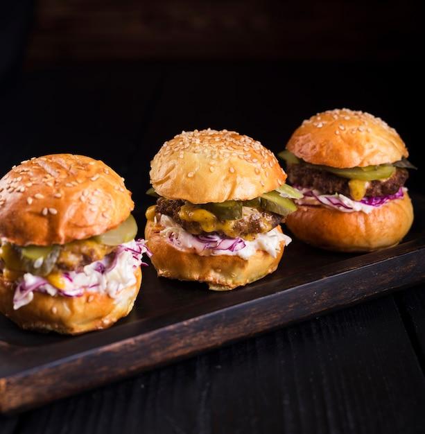 Набор вкусных гамбургеров на деревянной доске Бесплатные Фотографии