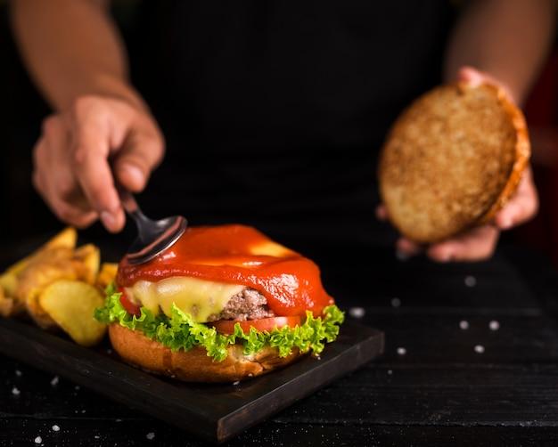 Мужчина разносит кетчуп на вкусный говяжий бургер Бесплатные Фотографии