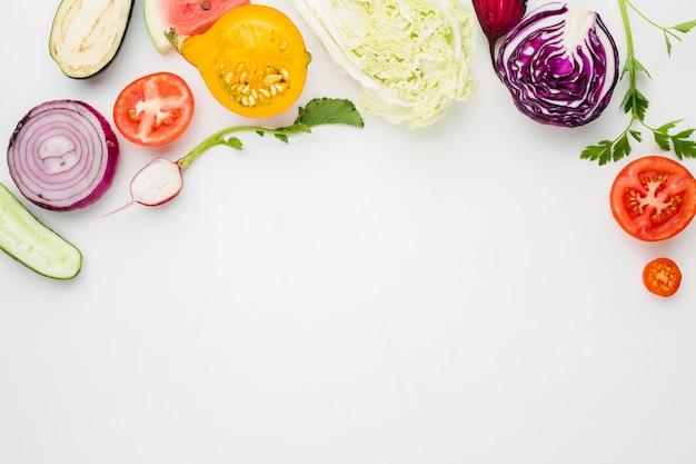 コピースペースで白い背景に野菜をスライスしたトップビュー 無料写真