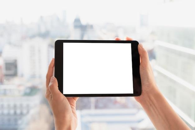 明るい背景とタブレットを保持している手 無料写真