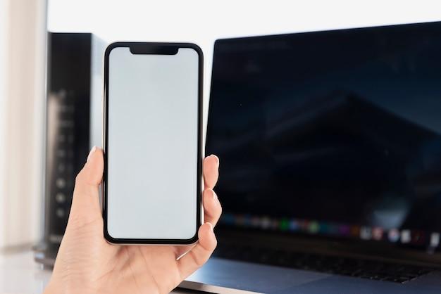 ノートパソコンのモックアップの前に電話を持っている手 無料写真