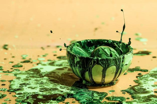 緑色の塗料スプラッシュとカップと抽象的な背景 無料写真