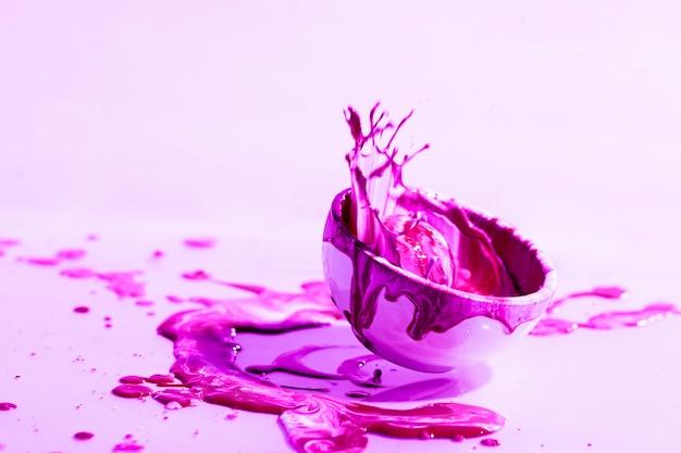 ピンクの塗料スプラッシュとカップと抽象的な背景 無料写真