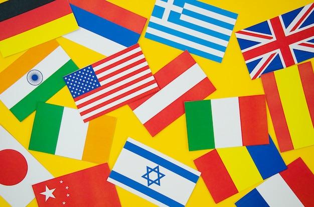 黄色の背景にさまざまな国の国旗 無料写真