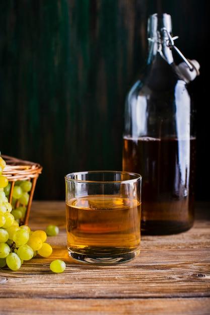 ボトルと新鮮なブドウジュースとテーブルの上のガラス 無料写真