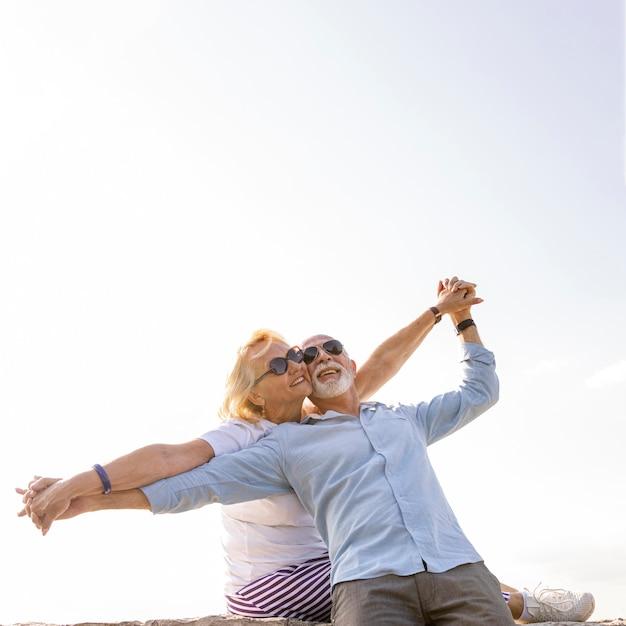 空中で腕を伸ばして幸せなカップル 無料写真