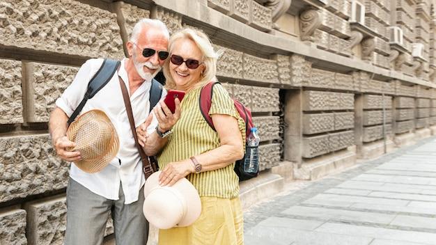 電話を見て幸せな老夫婦 無料写真