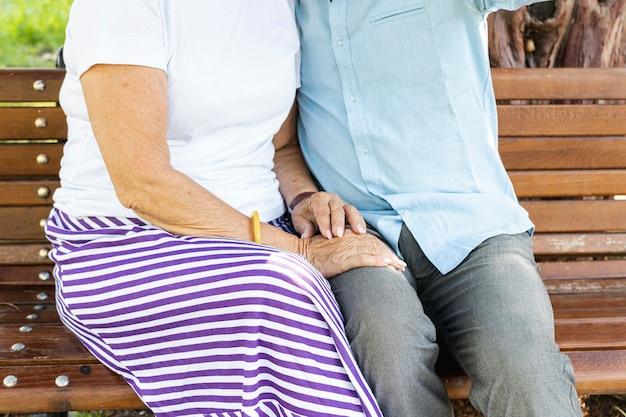 ベンチのクローズアップに座っている老夫婦 無料写真