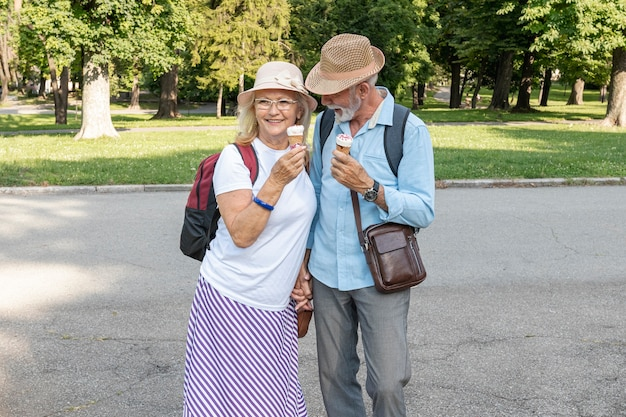 公園を歩いて手にアイスクリームをカップルします。 無料写真