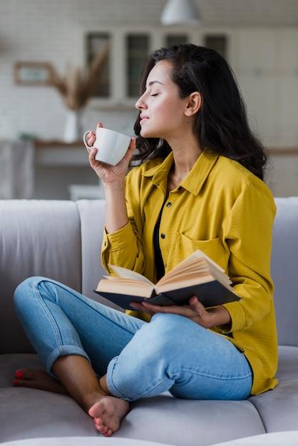 コーヒーを楽しむ本で完全なショットの女性 無料写真