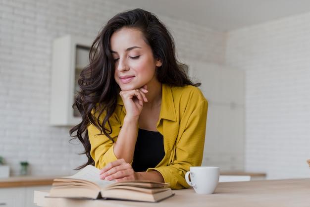 台所で読んでミディアムショット幸せな女 無料写真