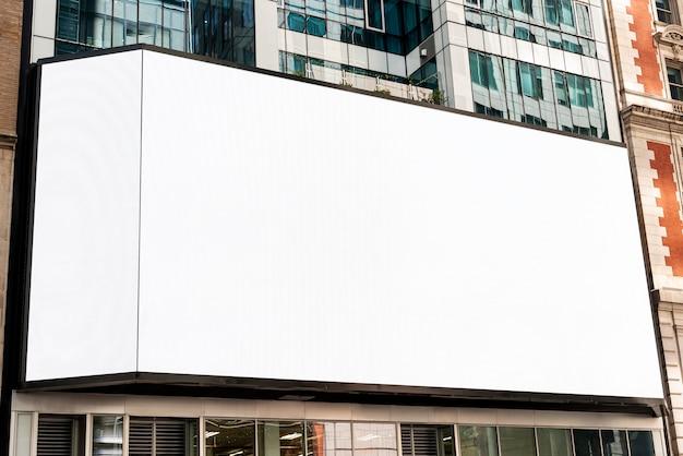 都市の建物に大きなモックアップ看板 無料写真