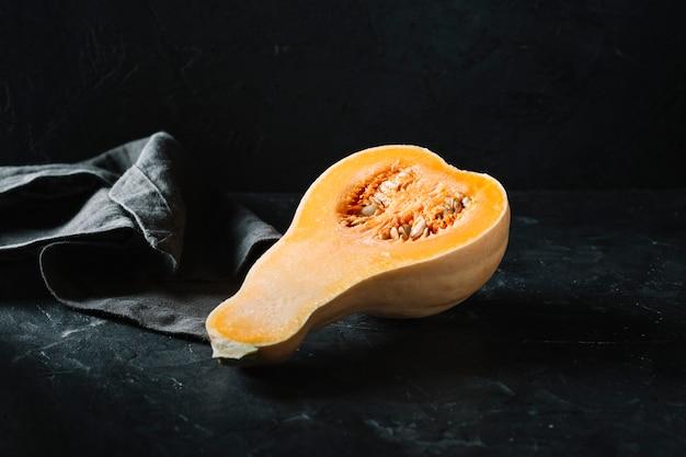 黒い背景に生の有機バターナットスカッシュの半分 無料写真