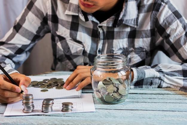 テーブルの上の貯金コインの瓶 無料写真