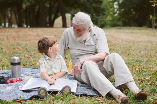 おじいちゃんと孫のピクニック読書 無料写真