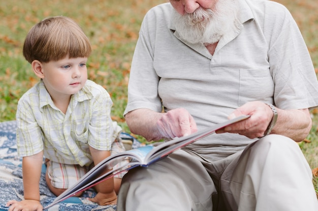 Дедушка читает внук на улице Бесплатные Фотографии