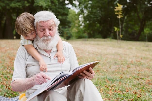 孫の正面のおじいちゃんの読書 無料写真