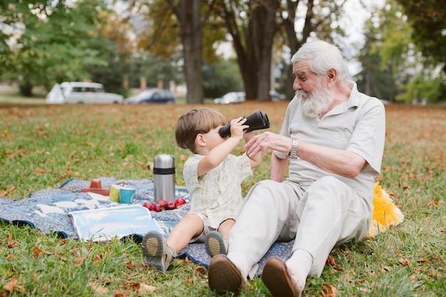 双眼鏡でおじいちゃんを見て孫 無料写真