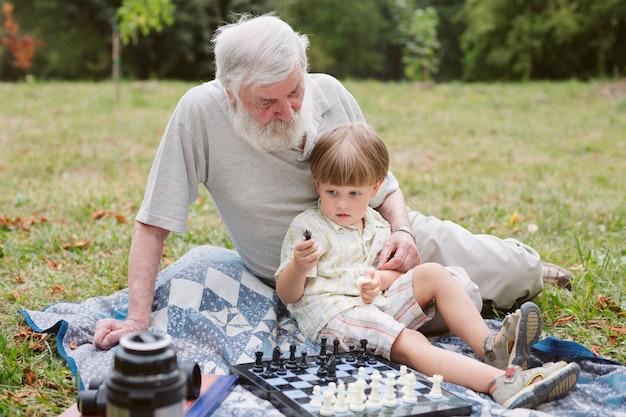 Вид спереди внук сидит с дедушкой Бесплатные Фотографии