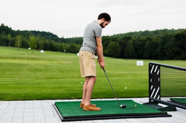 ゴルフ場で練習するプロのゴルフプレーヤー 無料写真