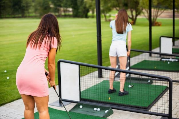 ゴルフを練習する女性のフルショット 無料写真
