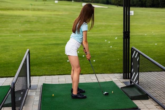 ゴルフを練習している女性の背面図 無料写真