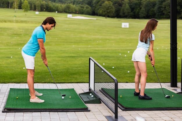 スイングを練習するバックビューゴルフプレーヤー 無料写真