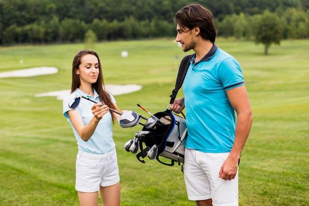 クラブを見ているゴルフプレーヤーの正面図 無料写真