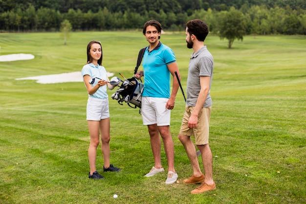 ゴルフコースで楽しんでいる友人のグループ 無料写真
