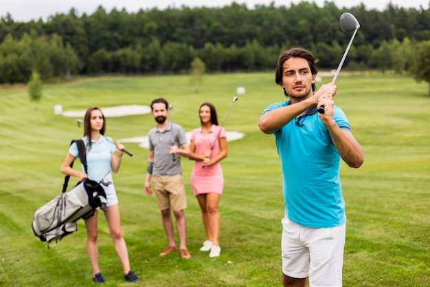 フィールドでゴルフをする友人 無料写真
