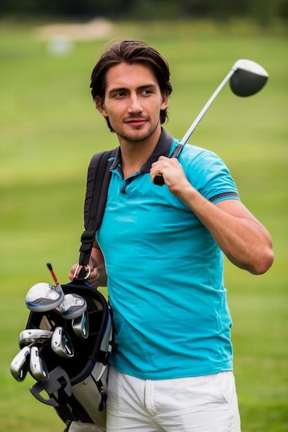 屋外でゴルフクラブを運ぶ大人の男 無料写真