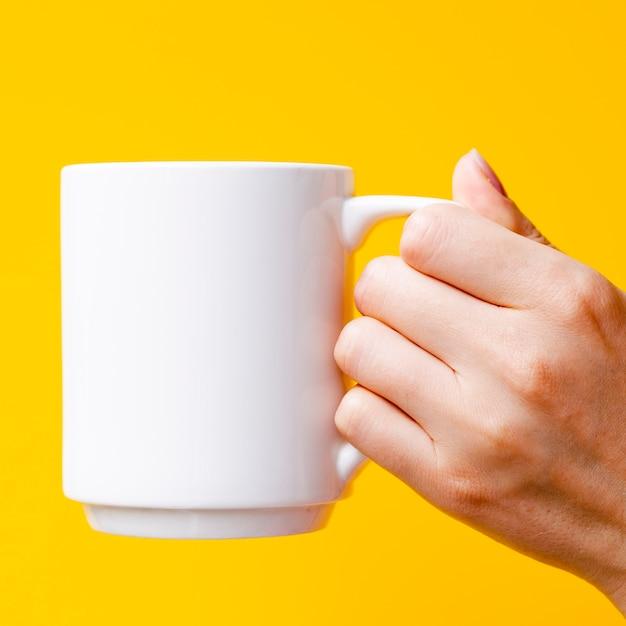 マグカップと黄色の背景を持つクローズアップ人 無料写真