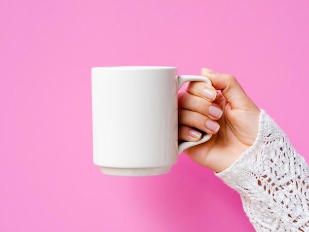 マグカップとピンクの背景を持つクローズアップ女性 無料写真