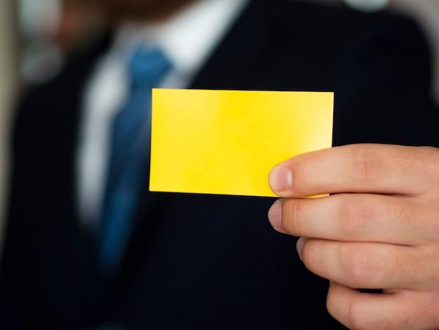 黄色の名刺とスーツを着たクローズアップ男 無料写真