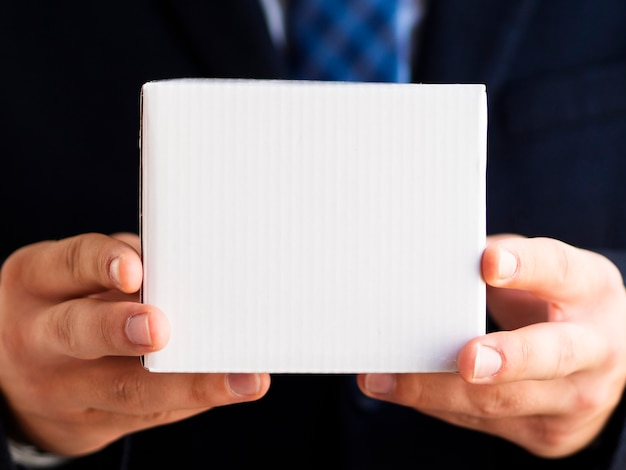 小さな箱を持ってクローズアップエレガントな男 無料写真