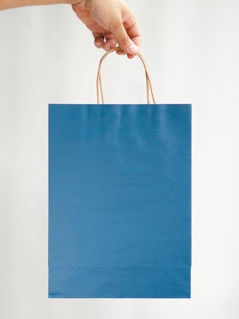 青い袋のモックアップを持っているクローズアップ手 無料写真