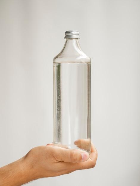 水のボトルのモックアップを持っているクローズアップ手 無料写真