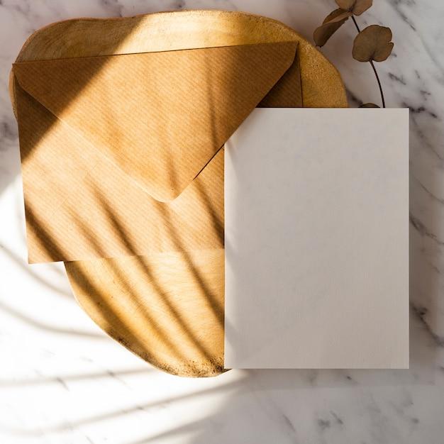 茶色の封筒と葉の影と大理石の背景に白い空白の木製のログと葉の枝 無料写真