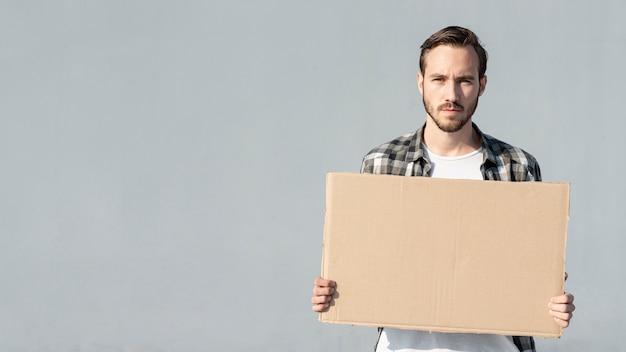 Молодой человек держит доску с макетом Бесплатные Фотографии