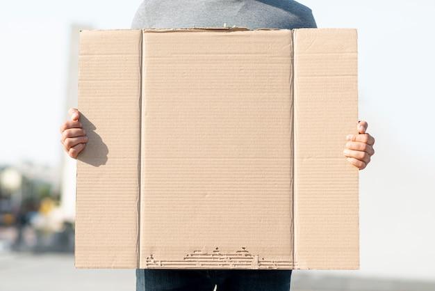 Протестующий держит картон с макетом Бесплатные Фотографии