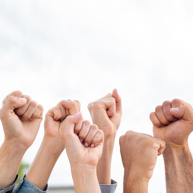 拳を掲げている活動家のグループ 無料写真