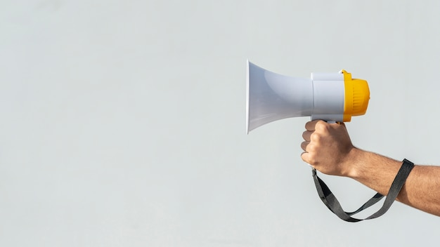 抗議のためのメガホンを持っている手 無料写真
