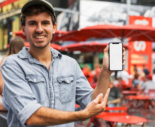 スマートフォンを指してスマイリー男 無料写真