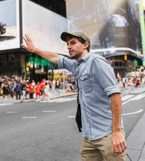 タクシーを止めようとしている若い男 無料写真
