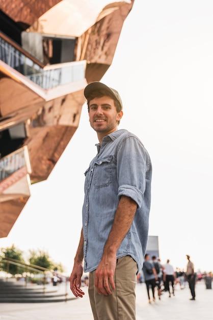 Молодой человек улыбается возле высокого здания Бесплатные Фотографии