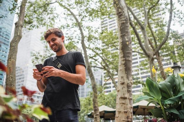 電話の画面を見ながら笑っている若い男 無料写真